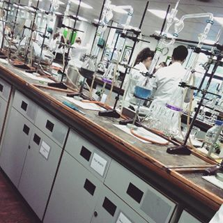 Inside the chemical analysis lab in the School of Food Science & Nutrition. Stands holding a variety of equipment including various flasks, burettes, & pipettes are set up on the work top. Two people in lab coats can be seen working in the background.
