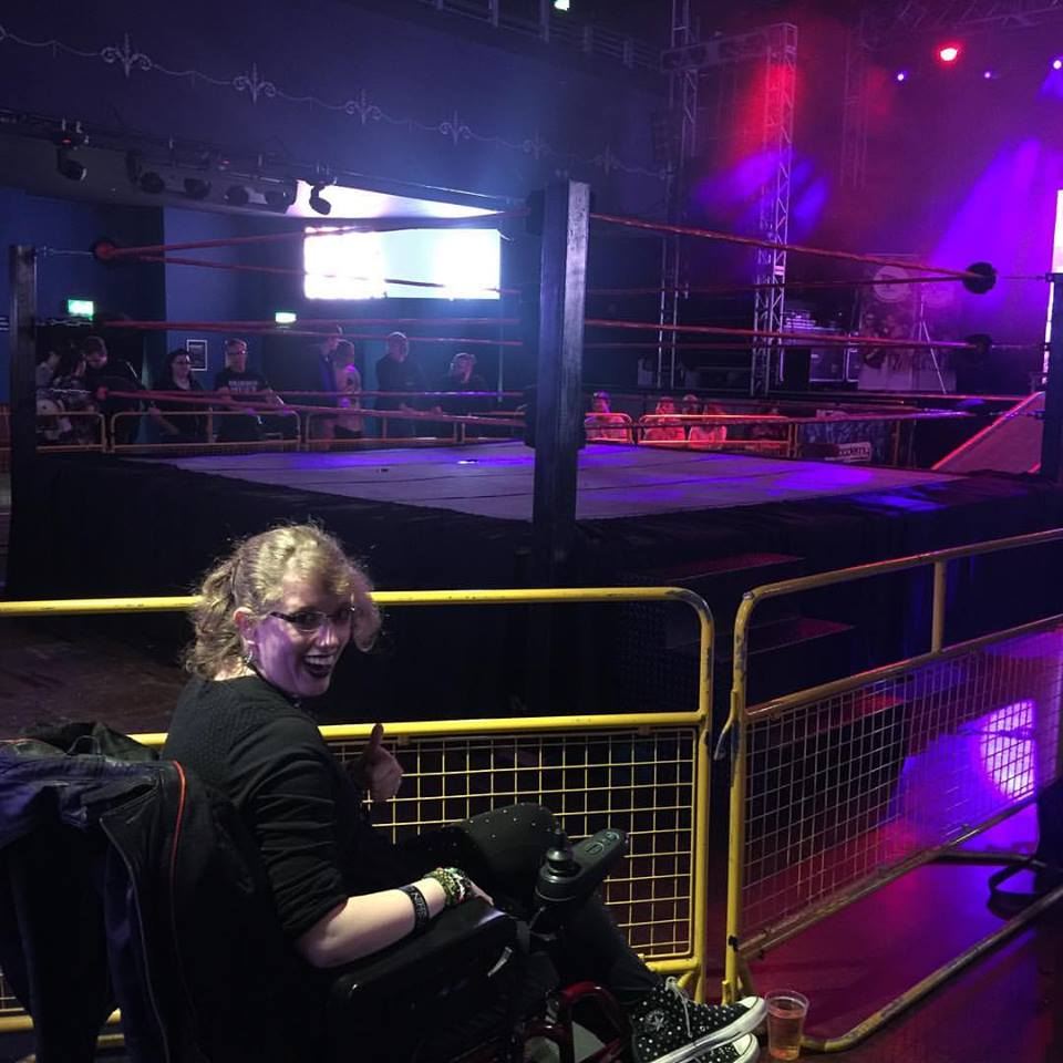 I'm sat in my powered wheelchair, looking back over my should at the camera, in the bottom left of the photo. In the background a wrestling ring & barriers can be seen. This was taken just before the wrestling show began, so the stage lights are on giving everything a purple tint.