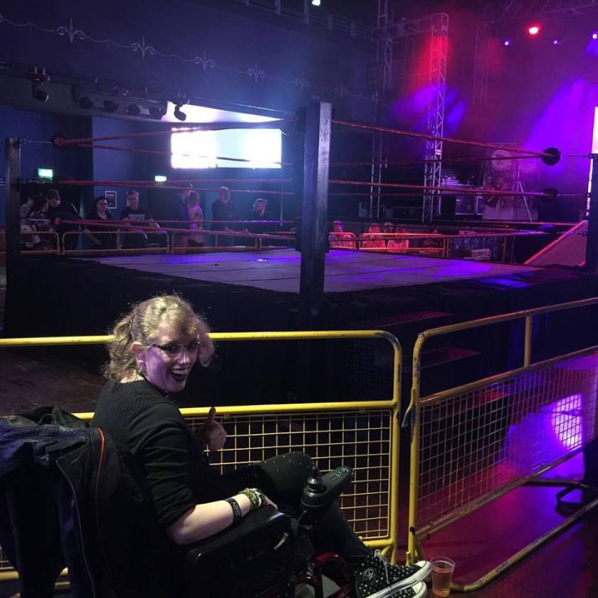 Image description: I'm sat in my powered wheelchair, looking back over my should at the camera, in the bottom left of the photo. In the background a wrestling ring & barriers can be seen. This was taken just before the wrestling show began, so the stage lights are on giving everything a purple tint.