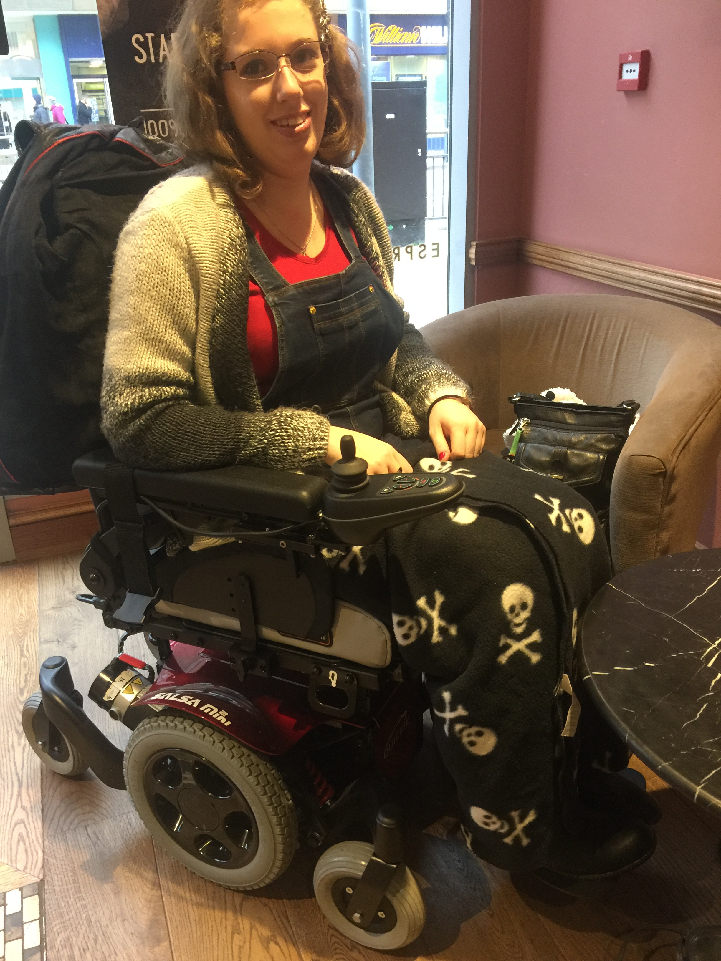 Image description: I'm sat in my powered wheelchair in a coffee shop. I have my skull and crossbones blanket on my knee, and my red top & dark blue pinafore are visible beneath my chunky knit cardigan.