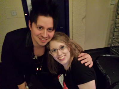 Image description: Harry from Yashin with his arm around me, smiling up at the camera for a photograph. I'm wearing my ghost-busters t-shirt. This was taken backstage due to the wheelchair access route, just before the gig kicked off.