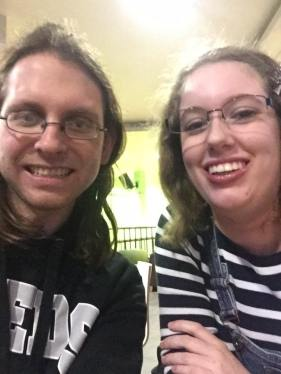 Image description: A selfie of myself & my husband as students. I'm wearing a navy blue & white striped jumper & blue dungarees, & Jarred is wearing a black University of Leeds hoodie.