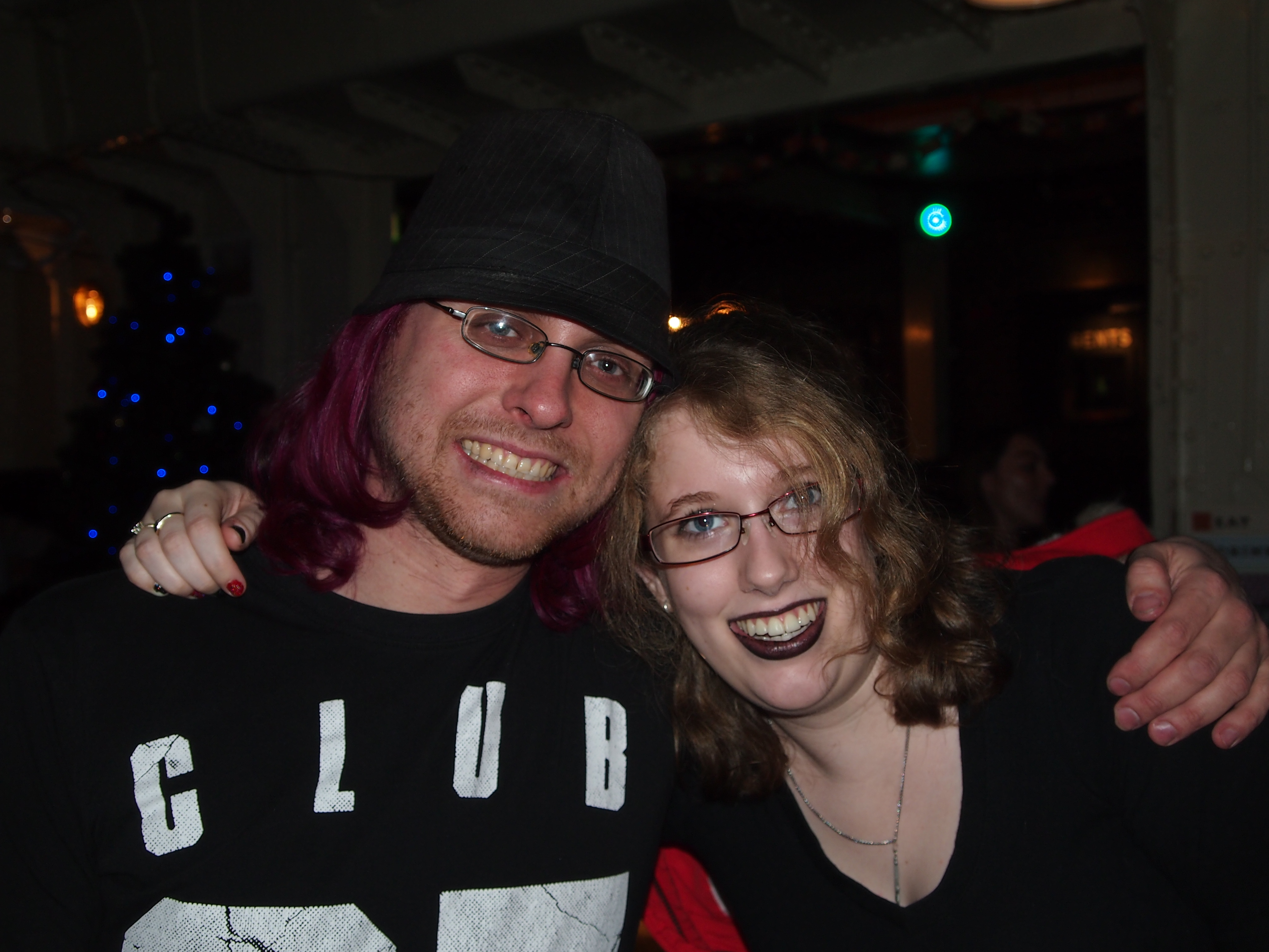 My husband & I when we were students, sat in a local bar at Christmas time. The room is fairly dark but you can see a Christmas tree in the background. We're facing the camera with our arms around each others shoulders.