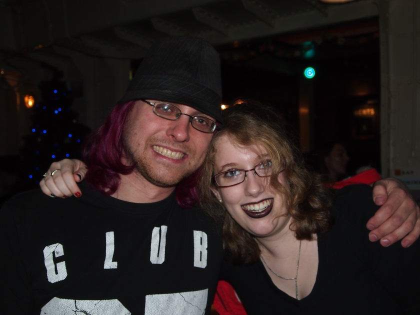 Image Description: my husband & I when we were students, sat in a local bar at Christmas time. The room is fairly dark but you can see a Christmas tree in the background. We're facing the camera with our arms around each others shoulders.