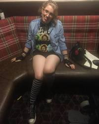 Image description: sat in a local bar as a student. I'm wearing black converse with silver spots on, black & white striped knee socks, black shirts, a Green Day t-shirt, & a denim shirt worn like a cardigan.
