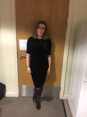 Image description: stood up in my student residence. I'm wearing black heels, plum-coloured tights, & a plain black dress. The dress is made of a velveteen material and is form-fitting. My hair is straightened and loose.