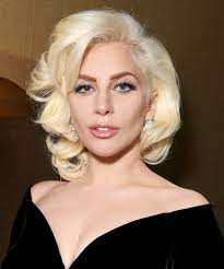 Image description: Lady Gaga where a black dress with a plunging neckline, and neatly styled blonde hair.