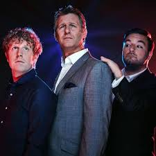 Image description: the 3 hosts of The Last Leg. On the left is Josh Widdecomb, Adam Hills is in the centre, & Alex Brooker is on the right.