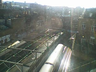 Image description: the view from the hotel window overlooking the train tracks as a tube train speeds underneath us.