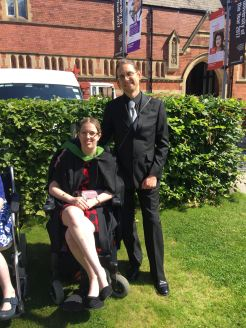 Image description: myself & my husband at my graduation. We're outside on a lawn by the student union as it was a hot day.