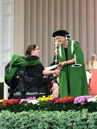 Image description: accepting my degree certificate. My green hood is draped over the back of my wheelchair chair.