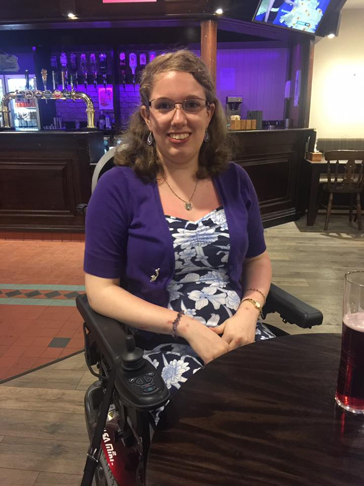 Image description: Sat in my powered wheelchair in a student bar. I'm wearing a blue dress with large flowers printed on, with a purple cardigan. My hair is half-up, half-down. This was taken on my 21st birthday.