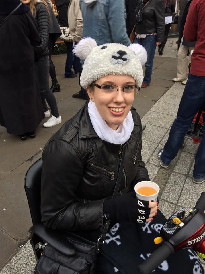 Image description: I'm sat on my mum's scooter as my wheelchair was broken at the time. I have my skull and crossbones blanket, my leather jacket, & am holding a cup of hot honey mead in my gloved hands. I'm wearing my beloved polar bear hat and smiling at the camera. It's one of my favourite photos of myself.