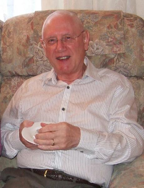 My grandfather on his golden wedding anniversary, sat on the sofa in his living room. He's holding a plate of food from the buffet and smiling at the camera.