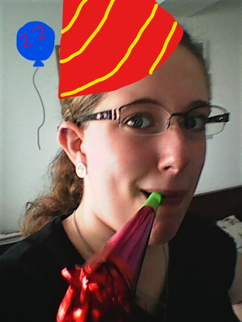 Image description: a selfie taken with a party-blower in my mouth. I edited on a party hat and balloon in MS Paint.