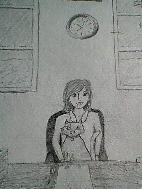 Image description: Sarah sat at her desk with Simon on her lap.