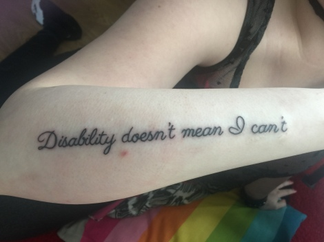 "Image description: holding my arm up to camera, showing the tattoo down my forearm reading ""disability doesn't mean I can't""."