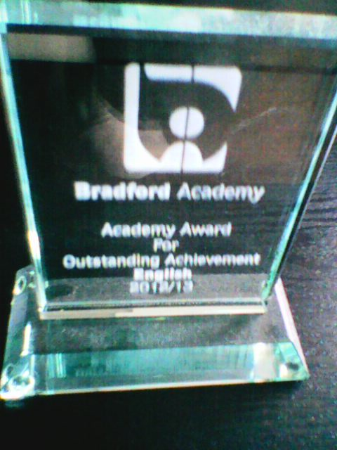 Image description: the English trophy I won for my GCSE English marks. It's glass & engraved with the school logo.