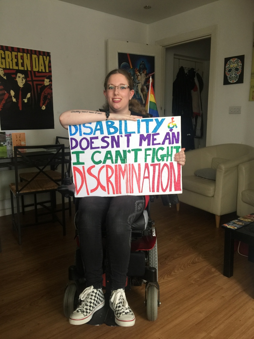 "Image description: about to head out to the local Trump protest. I'm sat in my wheelchair wearing black and white chequered converse & black skinny jeans. I'm holding my sign on my knee which reads ""Disability doesn't mean I can't fight discrimination""."