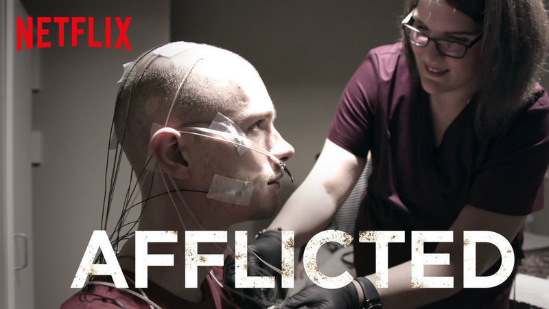 The image used to advertise the series. One of the participants sits side-on to the camera, covered in medical tubes & sensors for a diagnostic test. A nurse is leaning over him adjusting the tubes.