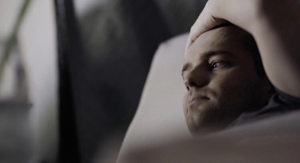 Image description: a shot of Jamison lying in bed, looking out of the window, taken from the show.