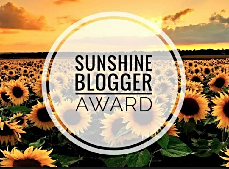 Image description: the Sunshine Blogger Awared logo. A white circle with the award's name placed over a field of sunflowers.