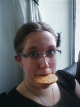 Image description: a selfie taken wearing a black t-shirt, with a chocolate chip digestive in my mouth.