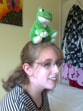 Image description: a photograph taken by my dad when I was a teenager, in my bedroom. I'm wearing a black and white striped t-shirt, & Croaky the frog is balanced on my head.