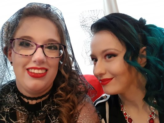 Sat on the sofa in front of the window with my bridesmaid, fully dressed for the wedding. I have silver eye shadow & red lipstick on, and the hood of my spider-web cloak is covering my curled hair. My bridesmaid has a similar hair do, and has red eye-shadow and lipstick to match her red dress. She has a red rose in her hair.