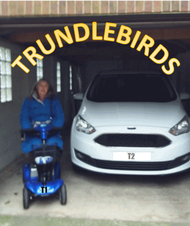 Image description: a photograph taken & edited by my dad looking into my parents garage. Mum is sat on her blue scooter next to dad's white car, with Trundlebirds written in yellow over the top of the image.