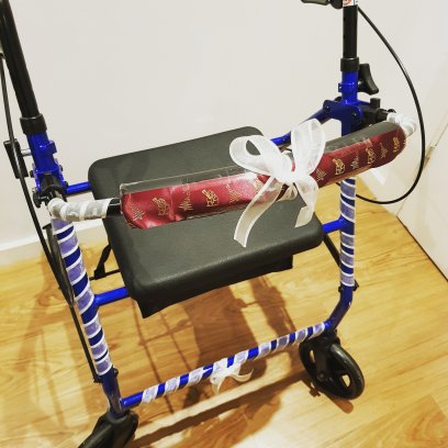 Image description: my royal blue rollator covered in silver & maroon ribbons.