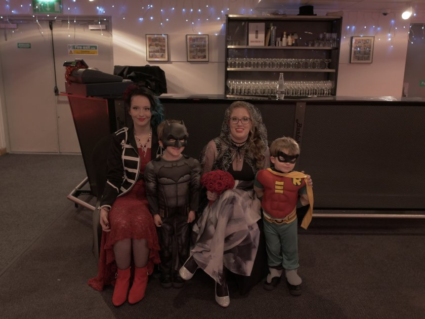 Image description: me & my bridesmaid sat with my two page boys, who were dressed as Batman & Robin.