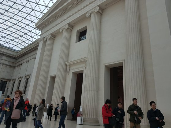 Inside the hall at the centre of the British Museum, looking up at the entrance to one of the galleries which is styled to look like an Ancient Greek temple.