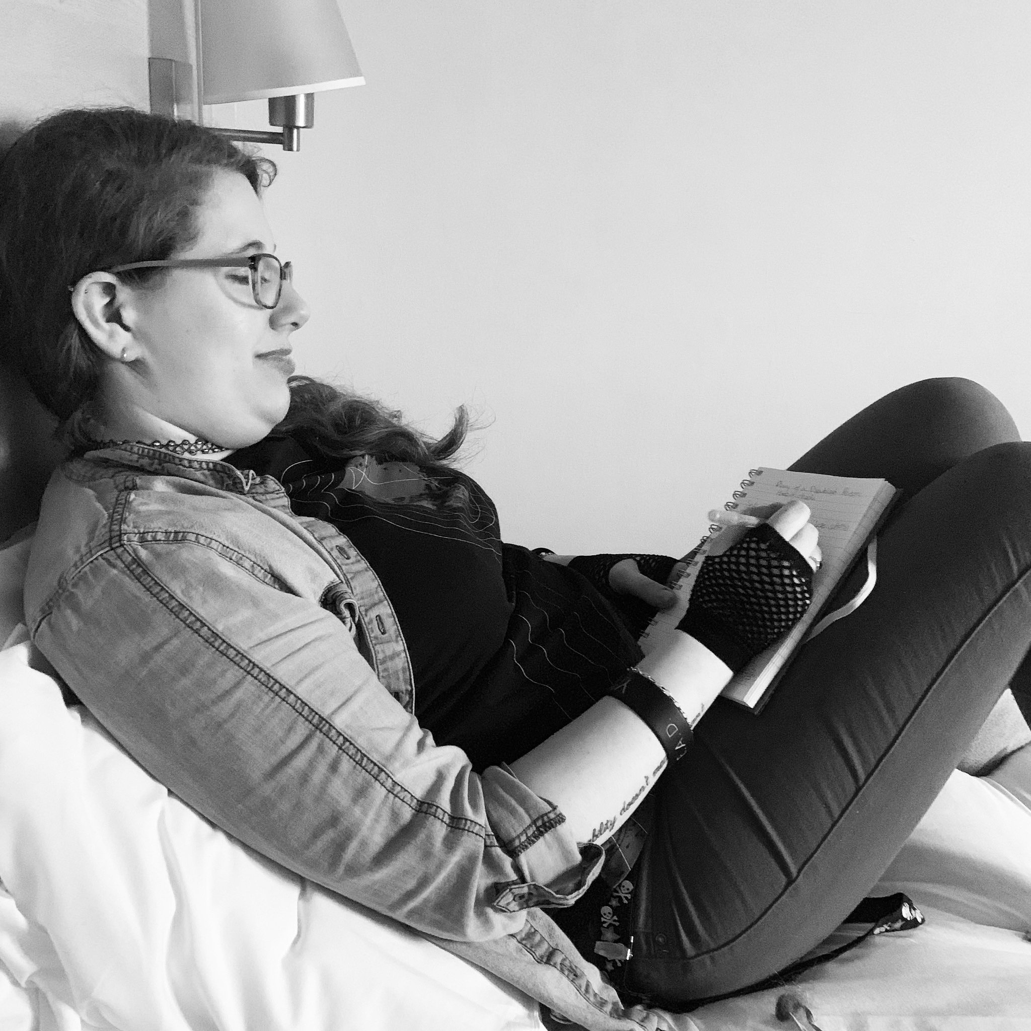 A black on white photograph of myself sat on the bed in the hotel room, leaning back on the pillows, scribbling some notes into my notebook in preparation for writing this blog post. I'm wearing jeans, a t-shirt, & a denim shirt.