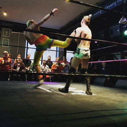 Chuck Mambo, another wrestler, super-kicking his opponent in the face in the middle of the ring.