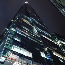 A photo taken from the base of the Shard, looking up the building into the night sky. Some of the lights are still on in the building.