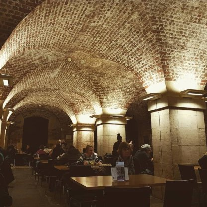 The Cafe in the Crypt: a large vault with a stone floor, & massive pillars & arches supporting the church above.