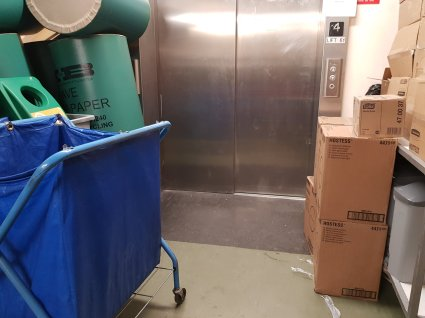 The lift blocked by crates, boxes, trolleys, & all manner of cleaning equipment.