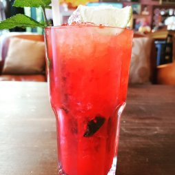 A red berry mojito, mint leaf included, in a tall glass.