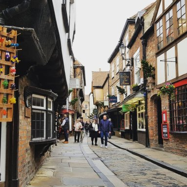 Sat on the cobbled pavement looking down the Shambles. Several people are milling around doing some shopping.