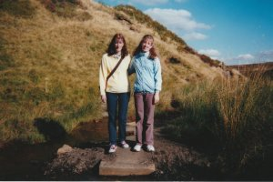 Stood with my mum, dressing in a yellow top & deep blue trousers, in the moors near Top Withins. We look very alike, with the same frizzy hair, & even tilting out heads the same way.