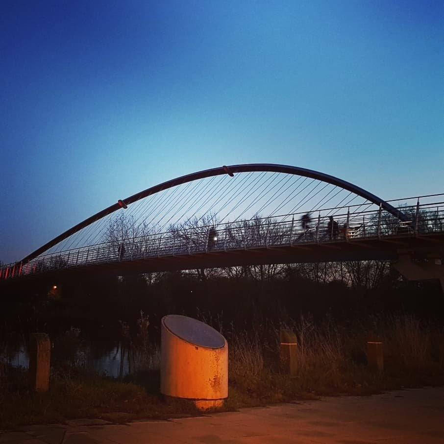 A modern bridge built at the millennium across the river Ouse. The sun is setting so it is silhouetted against the sky, taken looking up at the bridge from the river bank. You can see people crossing the modern suspension-style bridge.
