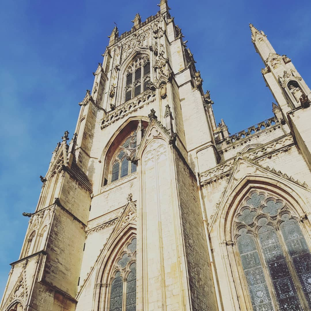 Looking up at one of the towers of York Minster from street level, in the morning sun. The detail of the windows & architecture is clearly visible.
