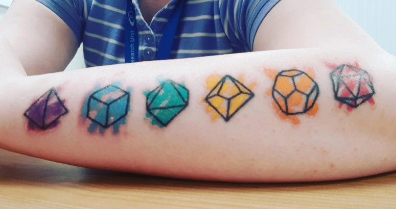 The outlines of Dungeons and Dragons dice from elbow to wrist in pride colours.