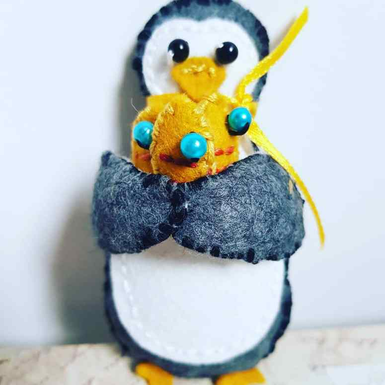 Another felt penguin, this time carrying three fish.