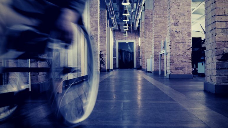 Blurred shot of a manual wheelchair moving towards the left of the camera down a corridor.