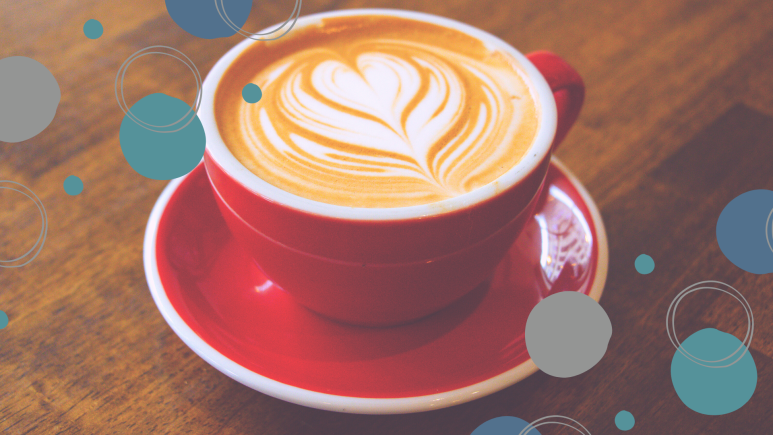 Latte in a red mug surrounded by a pattern of blue and grey dots.