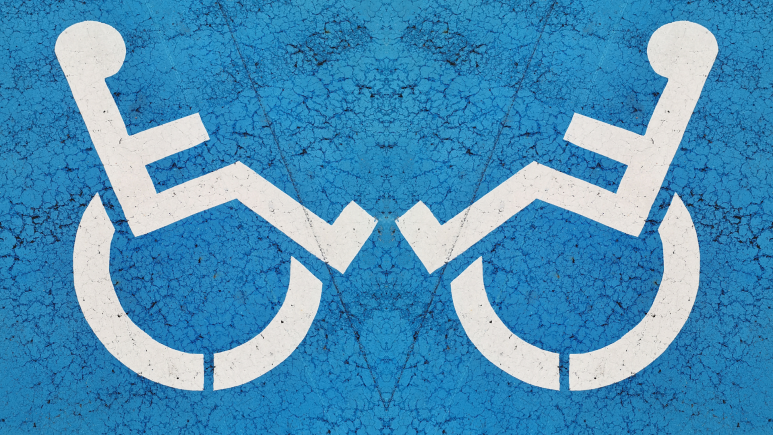 The classic disabled logo of a white stick figure using a wheelchair on a blue background, mirrored.