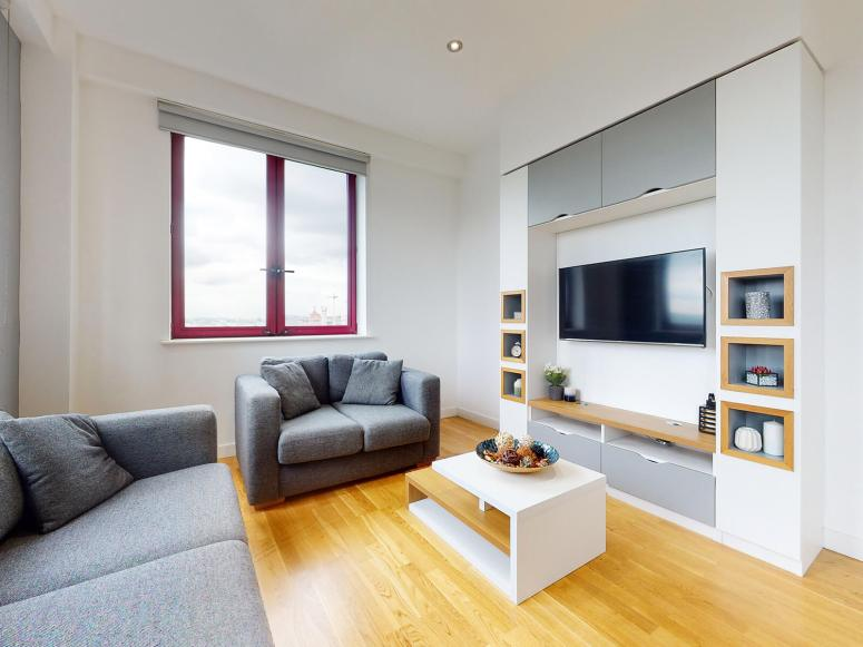 The inside of a living room similar to ours. Two grey sofas are arranged around a low coffee table, facing a wall-mounted TV and shelves. The floor is laminate.